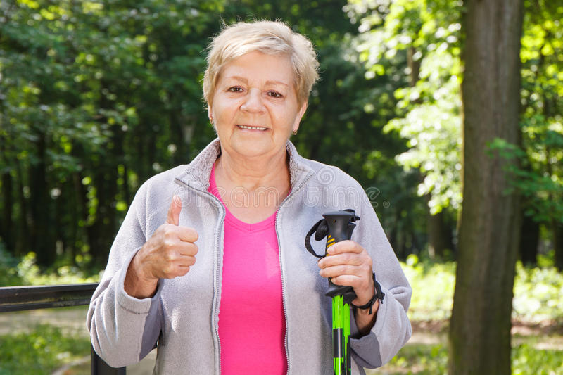 Elderly senior woman holding nordic walking sticks and showing thumbs up stock images