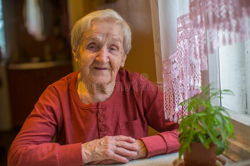 Elderly happy senior woman sitting at the table. Elderly senior woman sitting at the table stock photography