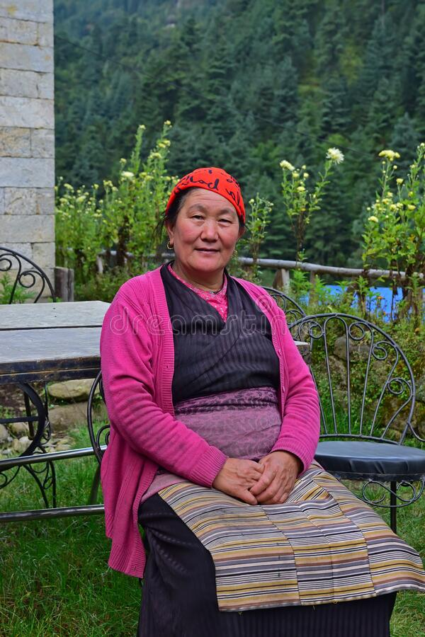 Free Elderly Sherpa Woman Who Works In A Local Hostel In Traditional Attire Sitting In The Home Garden Royalty Free Stock Image - 172654566