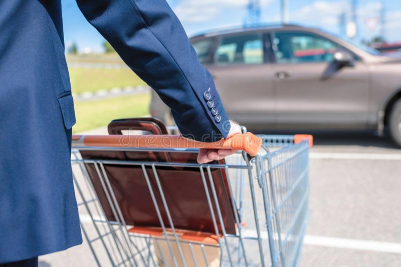 Elderly single man in a blue suit walks to his car with a supermarket trolley. Businessman and shopping. royalty free stock photo