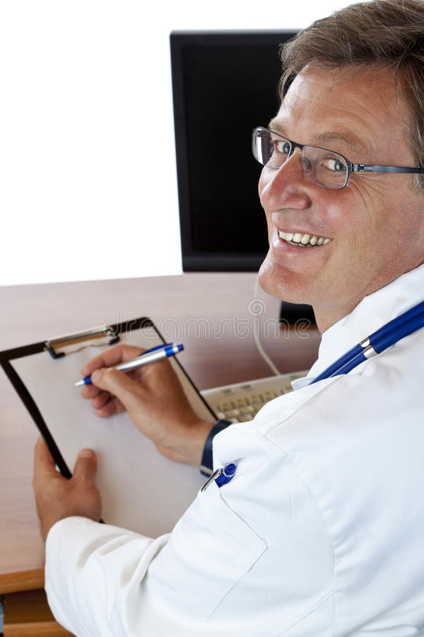 Elderly smiling doctor sits at his desk stock image