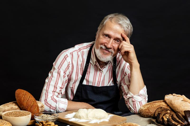 Elderly smiling professional chef man. Isolated over black background royalty free stock photo