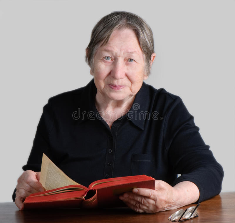 Elderly smiling woman. With book royalty free stock images