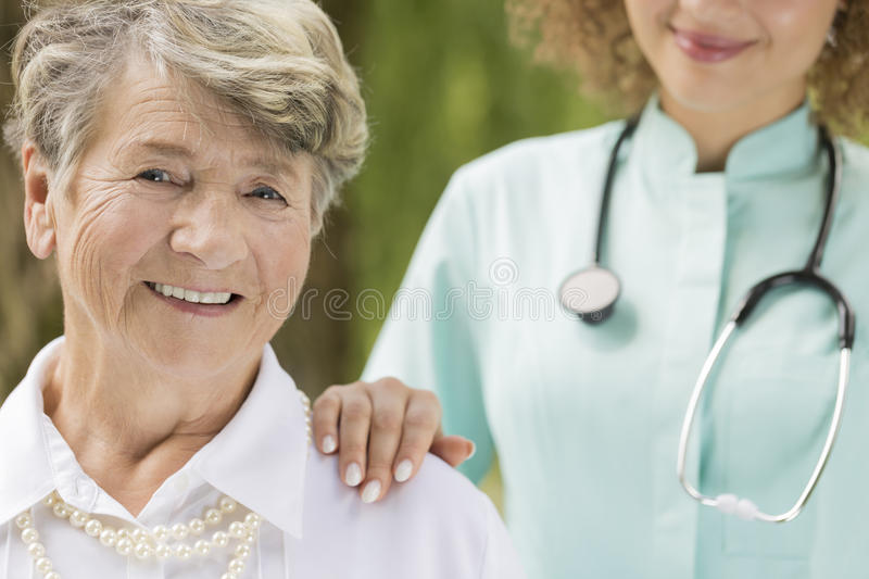 Elderly smiling woman with the doctor. Close shot of elderly, smiling women with the doctor`s hand on senior shoulder stock image