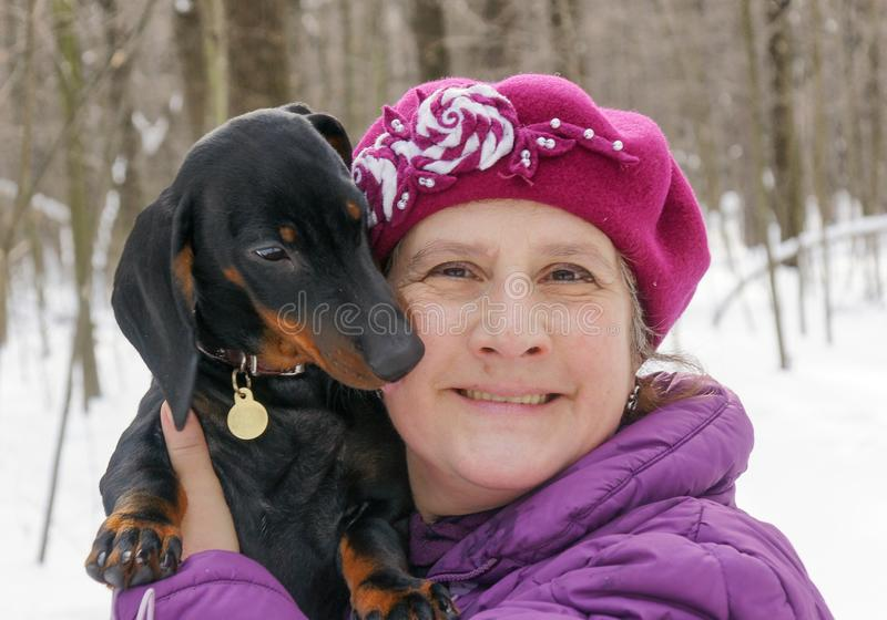 Elderly smiling woman holding puppy of dachshund in winter park. Elderly smiling woman holding three-month puppy of black and tan dachshund in winter park stock images