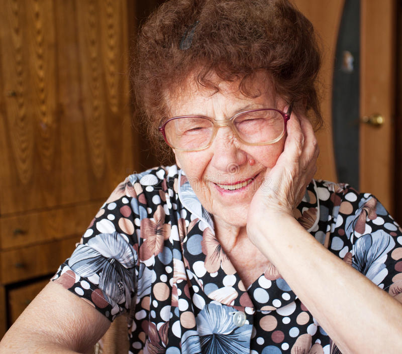 Elderly smiling woman at home. Old woman. Laughing elderly female at home royalty free stock images