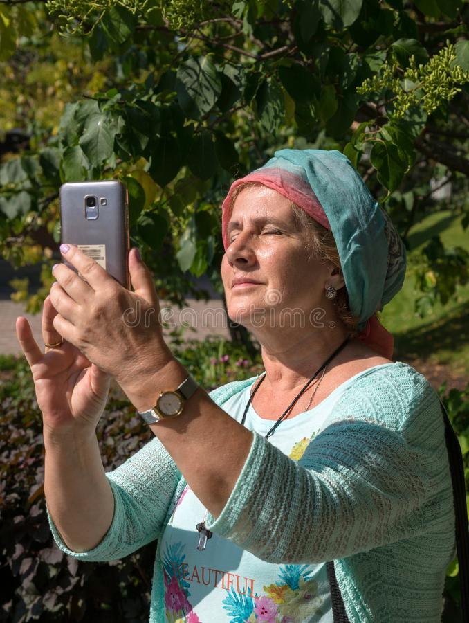 Elderly smiling woman makes selfie on smartphone in summer sunny day.  stock photo