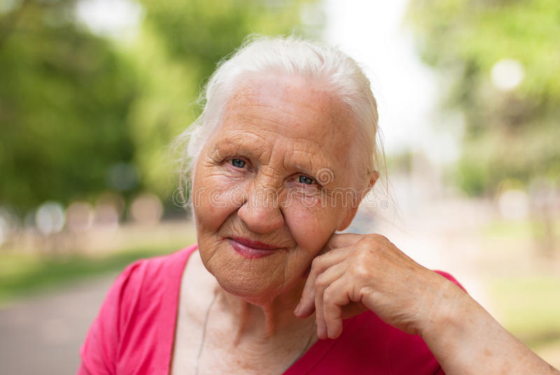 Elderly smiling woman. In a parc stock images