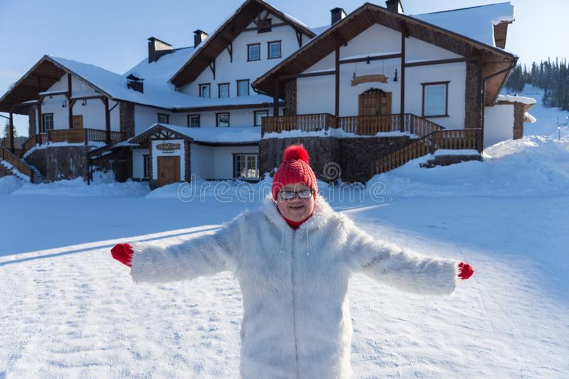 An elderly smiling woman stands with arms outstretched in front of the cottage, on a sunny winter day. Elderly smiling woman stands with arms outstretched in stock photo