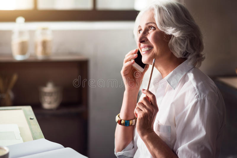 Elderly smiling woman talking on the phone. Hello dear. Smiling elegant elderly woman talking on cellphone while working with documents and sitting in the royalty free stock image