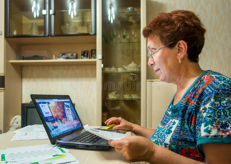 Elderly a smiling woman uses the online system of the bank to pay the bills stock images