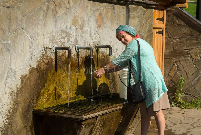 Elderly smiling woman washing an apple under water tap on summer sunny day.  stock image