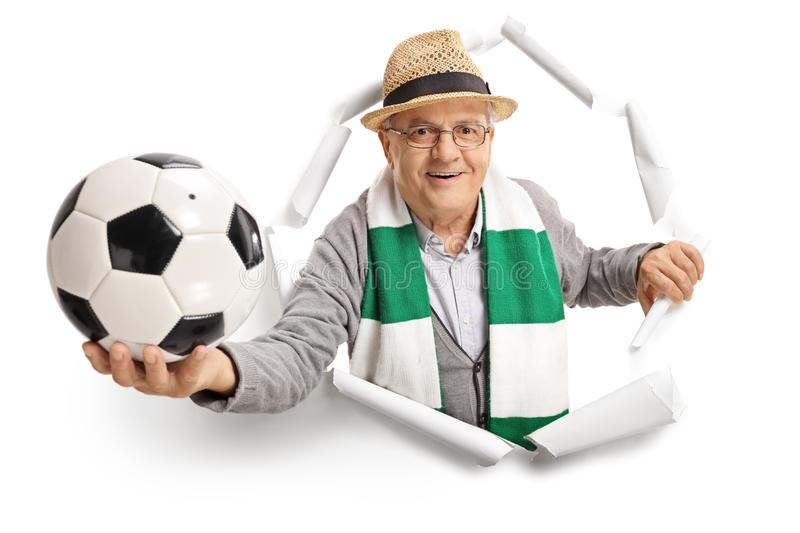 Elderly soccer fan breaking through paper stock photo