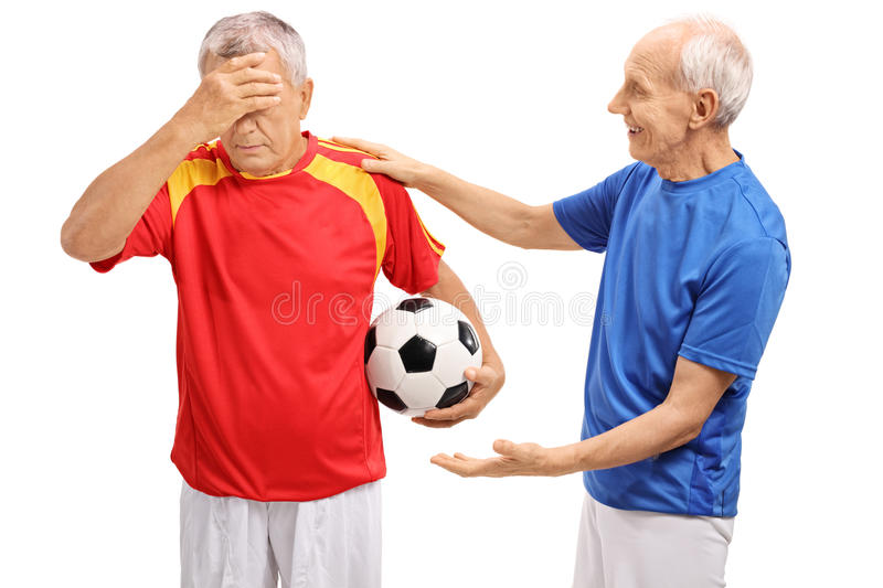 Elderly soccer player consoling another player royalty free stock images