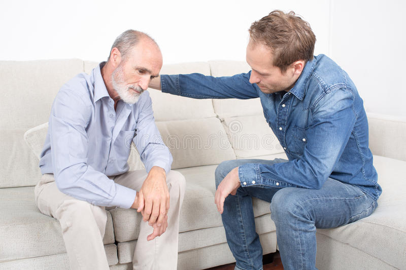 Elderly son comforting father royalty free stock photos