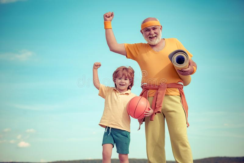 Elderly sporty man and young boy sporting morning workout - copy space. Young - old workout. Portrait of a healthy. Elderly sporty men and young boy sporting stock photos