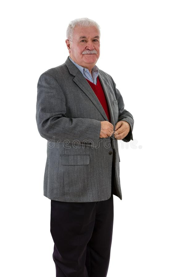 Elderly stylish man getting ready for a meeting. Standing buttoning up his jacket as he looks at the camera with a serious expression over white stock photos