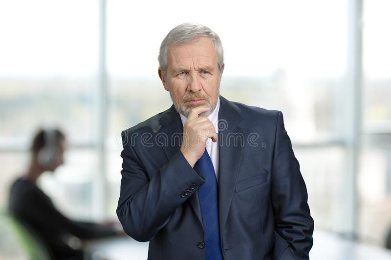 Elderly thoughtful businessman in bright office background. royalty free stock image
