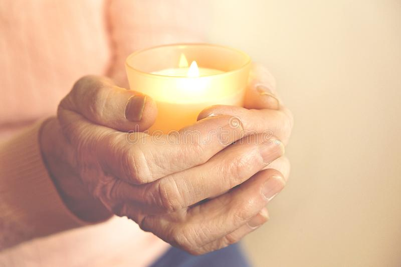 Close up of mature womans hands. Health care giving, nursing home. Parental love of grandmother. Old age related diseases. Elderly veteran woman holding burning royalty free stock images