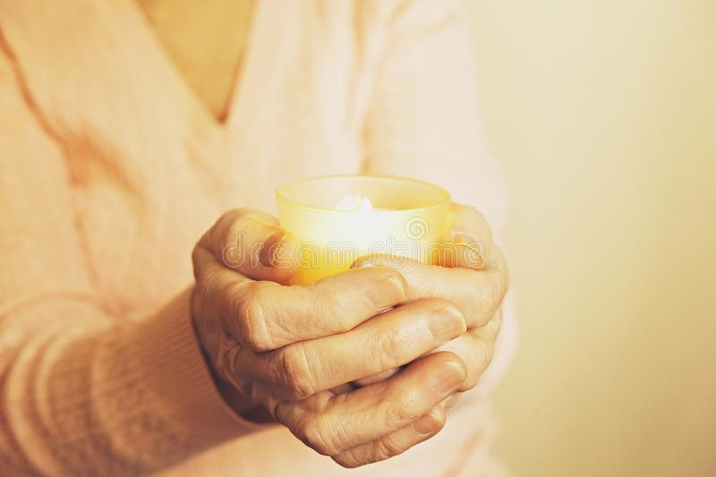 Close up of mature womans hands. Health care giving, nursing home. Parental love of grandmother. Old age related diseases. Elderly veteran woman holding burning royalty free stock image