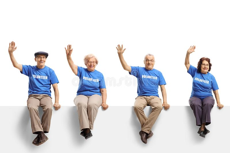 Elderly volunteers sitting on panel and waving. Full length shot of a elderly volunteers sitting on panel and waving isolated on white background stock images