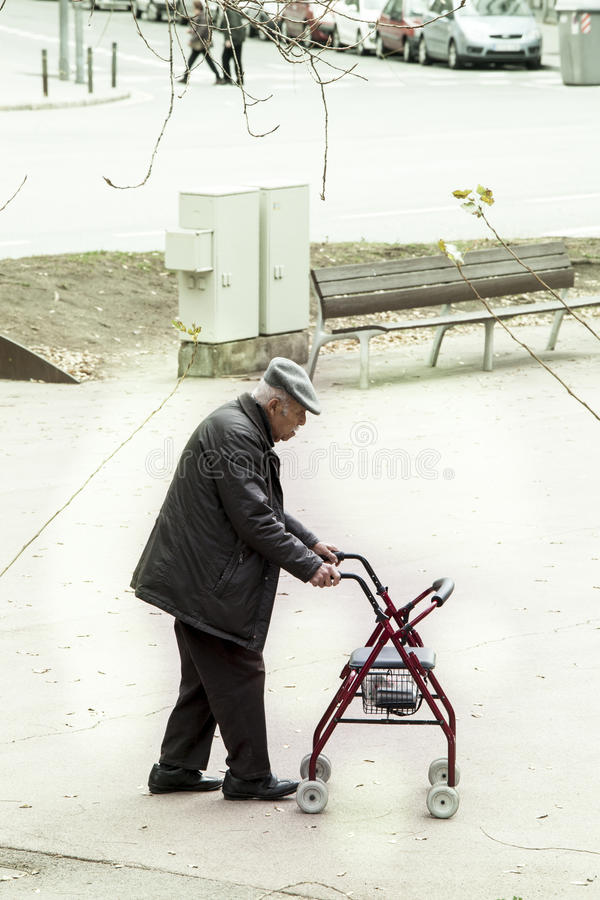 Elderly walking leaning on a small support cart stock photography