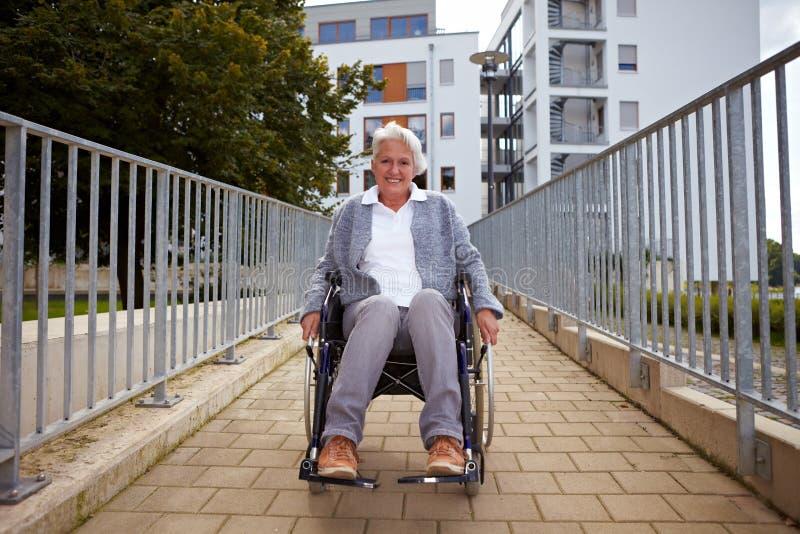 Elderly wheelchair user on ramp. Happy elderly woman in wheelchair using a ramp royalty free stock photography