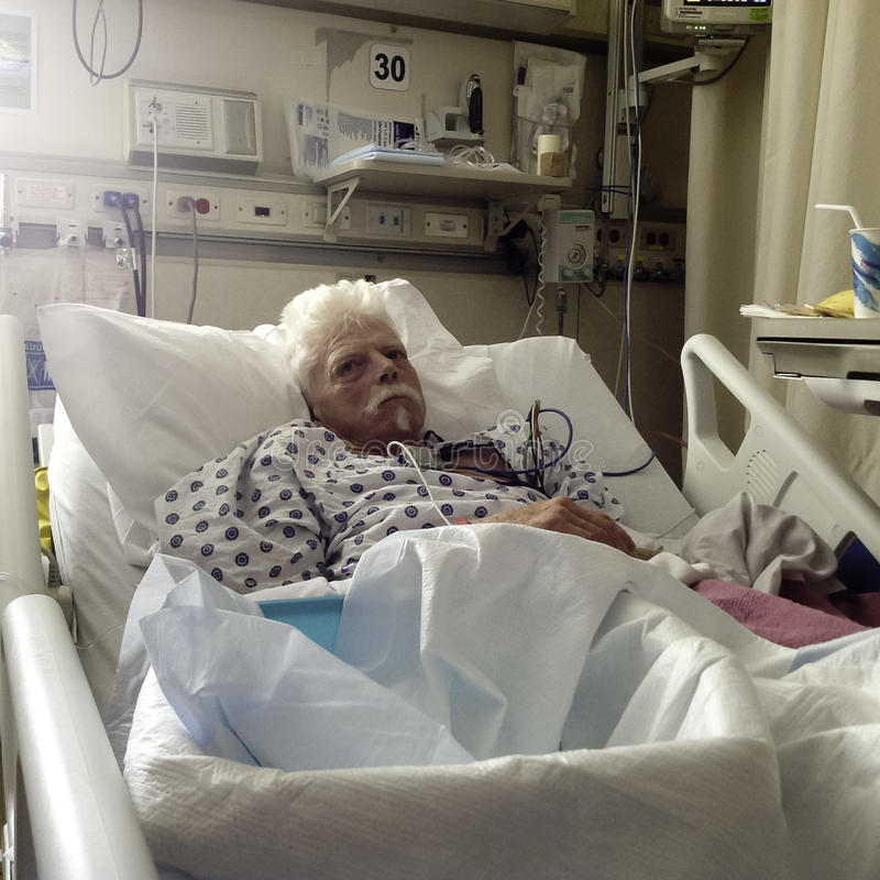 Elderly, white haired male patient in hospital bed stock photos