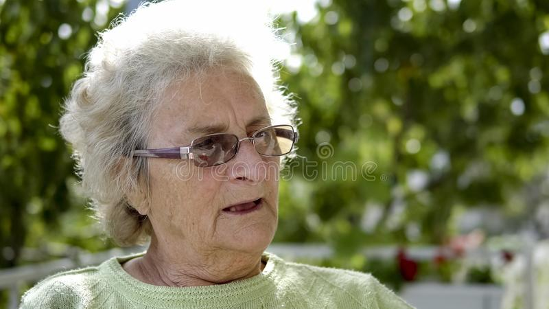 Elderly white woman looking off in the distance sadly. A close-up of a elderly white woman looking off in the distance sadly stock photos