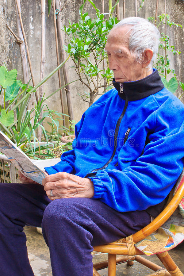 The elderly who Reading newspaper in the courtyard stock photos