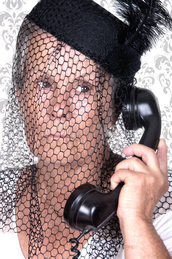 Elderly widow talking on old phone