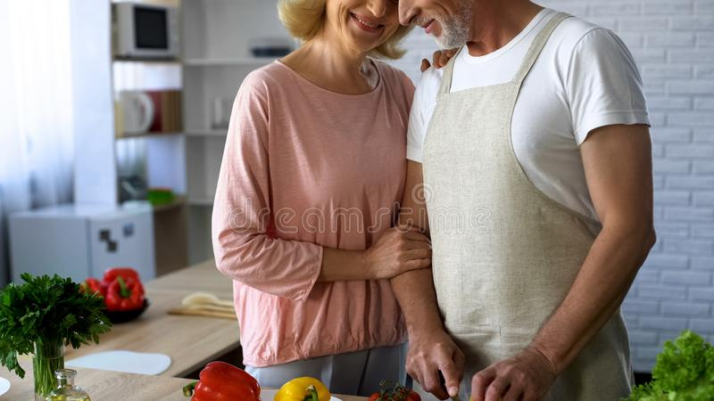 Elderly wife hugging husband, family cooking tradition, tender relations, love. Stock photo stock photography