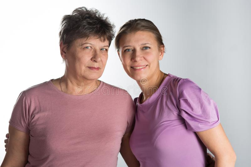 Elderly woman with adult daughter stock photo