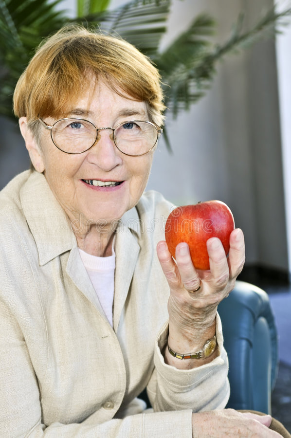 Elderly woman with apple royalty free stock image