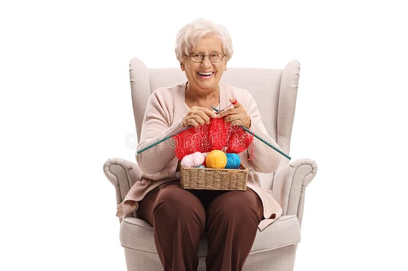 Elderly woman in an armchair knitting and smiling at the camera. Isolated on white background stock photography