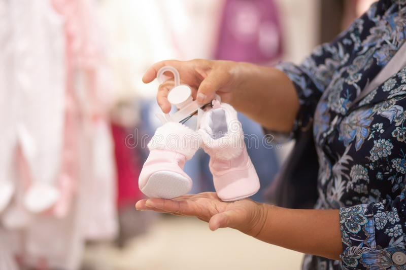 Elderly woman grandmother choosing baby clothes in the shop. Elderly woman in baby apparel store, buying tiny shoes for the newborn child, grandmother concept royalty free stock photography