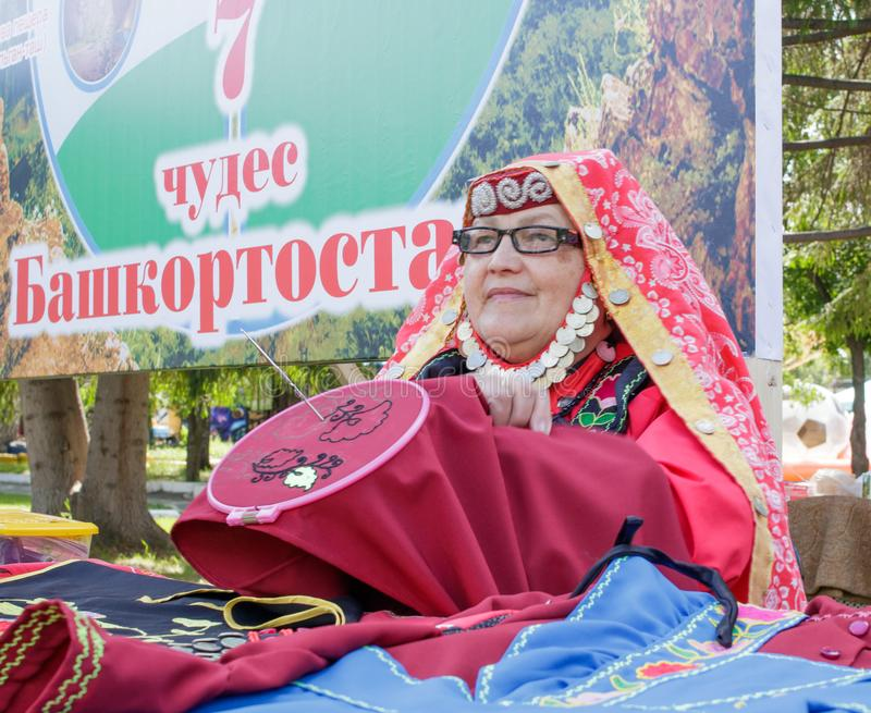 An elderly woman in Bashkir clothes embroiders a crochet pattern. Traditional national holiday Sabantuy in the city park royalty free stock photography