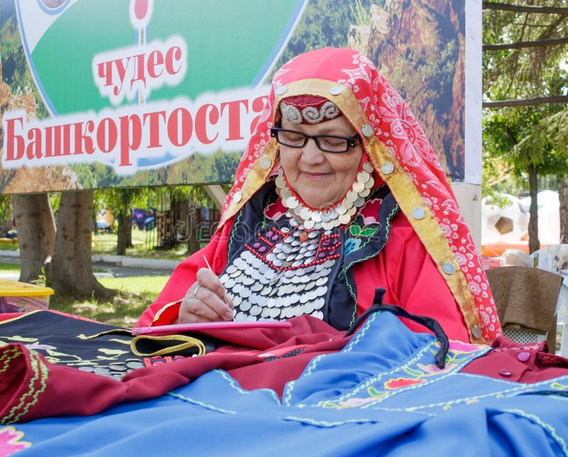 An elderly woman in Bashkir clothes embroiders a crochet pattern. Traditional national holiday Sabantuy in the city park royalty free stock photos