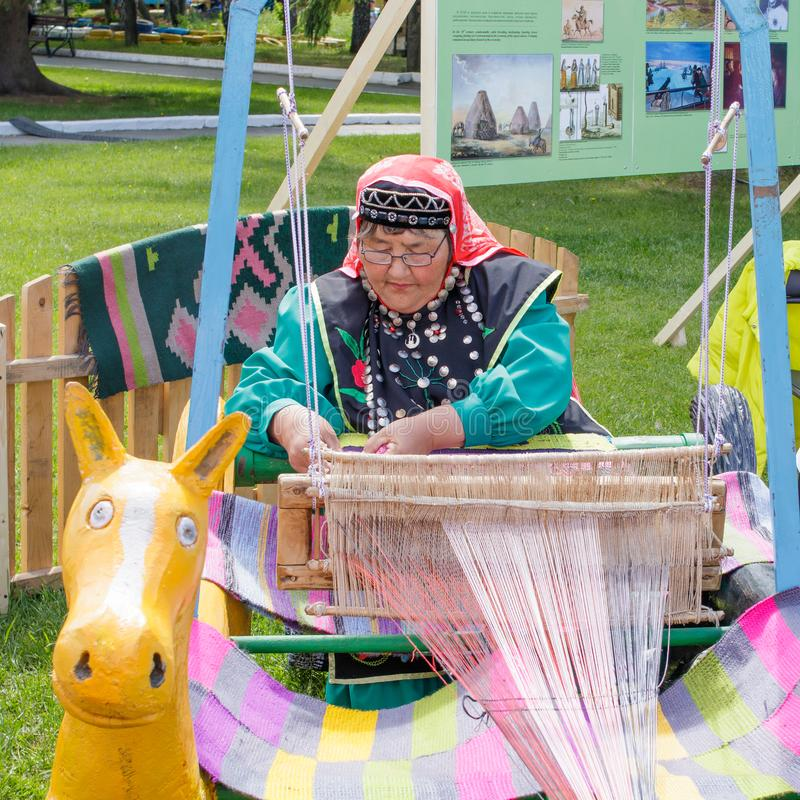 An elderly woman in Bashkir clothes is seated at a loom and weaves a carpet. National holiday Sabantuy in the city park stock photography