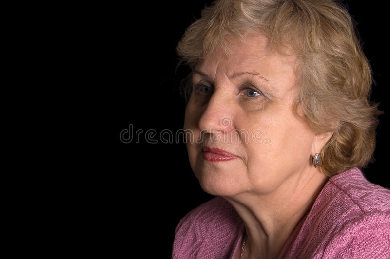 The elderly woman on black background stock image
