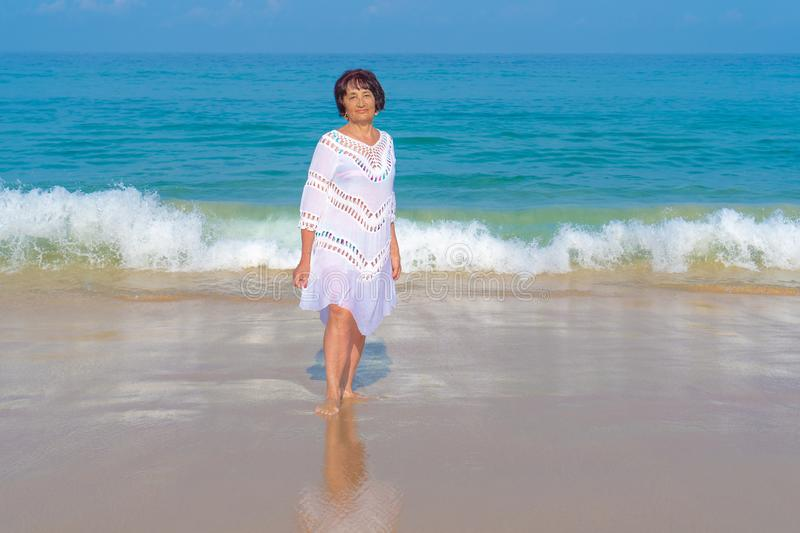 An elderly woman with black hair in white dress stand against the sea. Elderly people royalty free stock photography