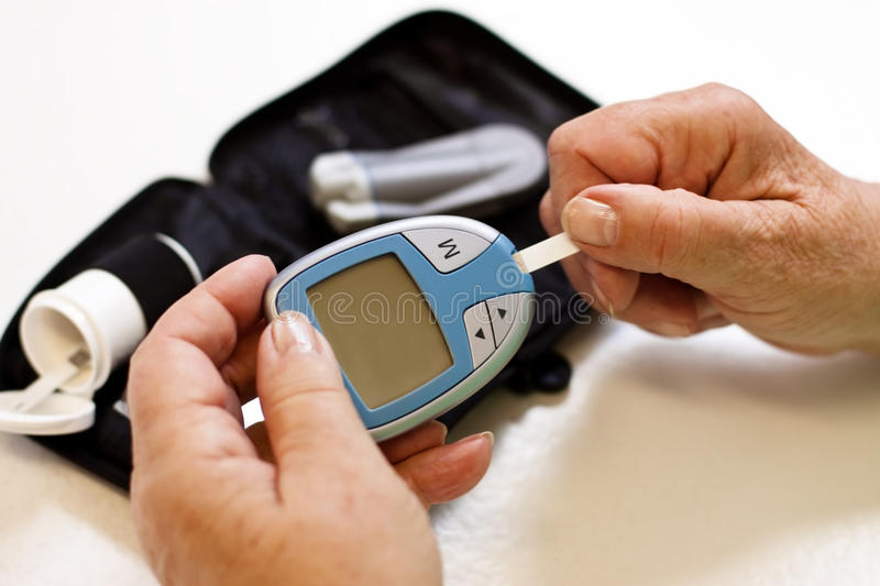 Elderly woman with blood sugar monitoring stock image