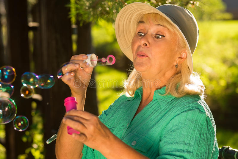 Elderly woman blowing bubbles. royalty free stock photos