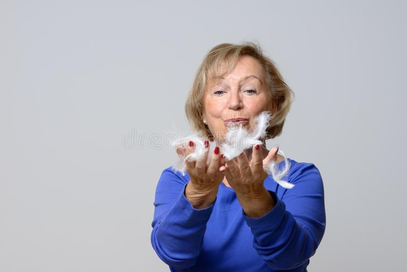 Elderly woman blowing white bird feathers stock photos