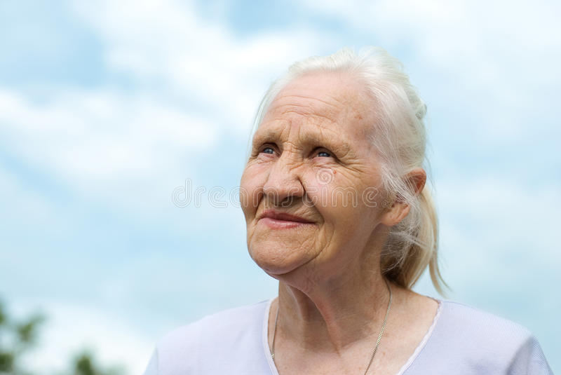 Elderly woman at the blue sky background
