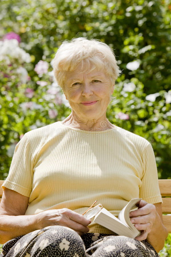 The elderly woman with the book stock photography