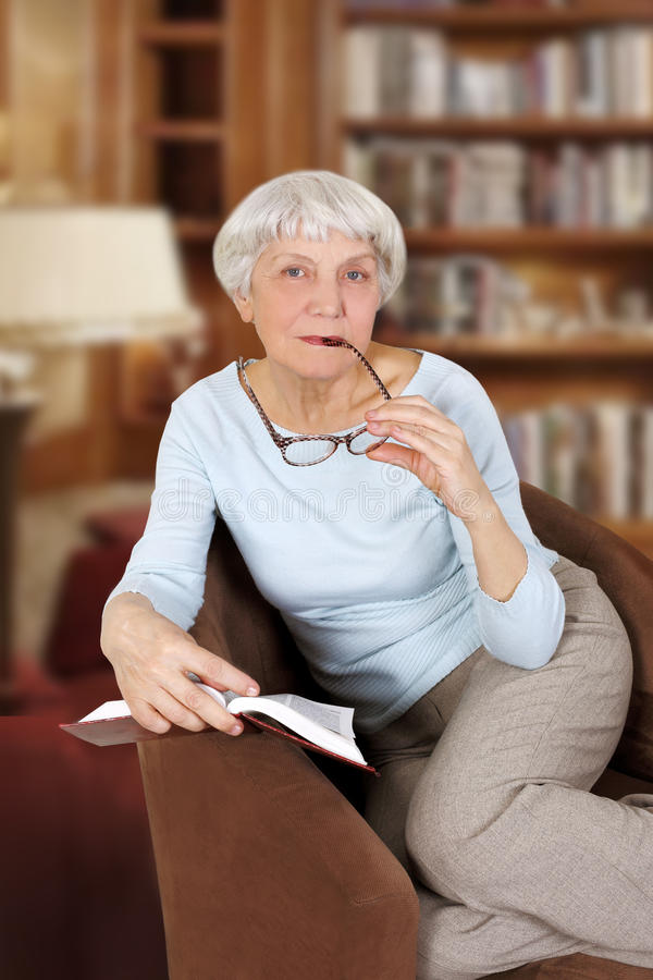 Elderly woman with book and glasses sitting in a chair royalty free stock image