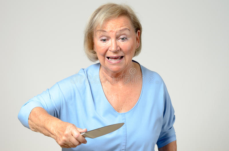 Elderly woman brandishing a kitchen knife. Emotional elderly woman brandishing a kitchen knife in her hand with a look of perplexed horror and shock, over grey royalty free stock images