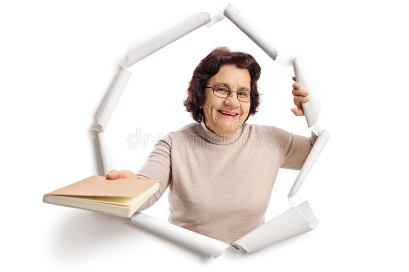 Elderly woman breaking through paper royalty free stock photos