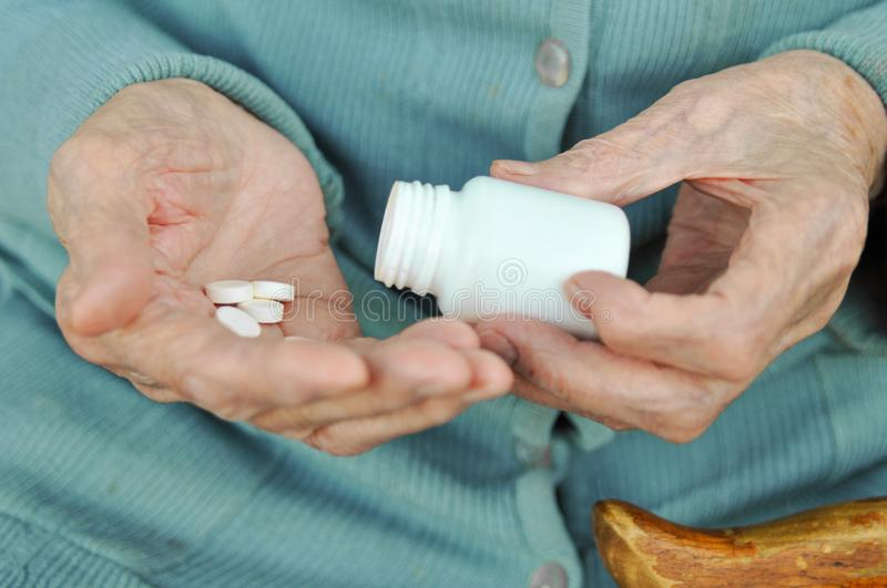 An elderly woman with a cane holding a pill and a container on the street. Health.Mockup. Close up. stock image